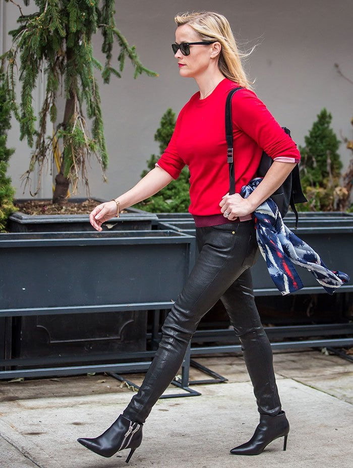 Reese Witherspoon rocksa bright red cashmere top with black skin-tight leather pants