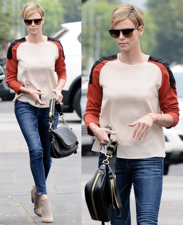 Charlize Theron stays trendy and cool in a color block shirt, jeans, and beige ankle boots