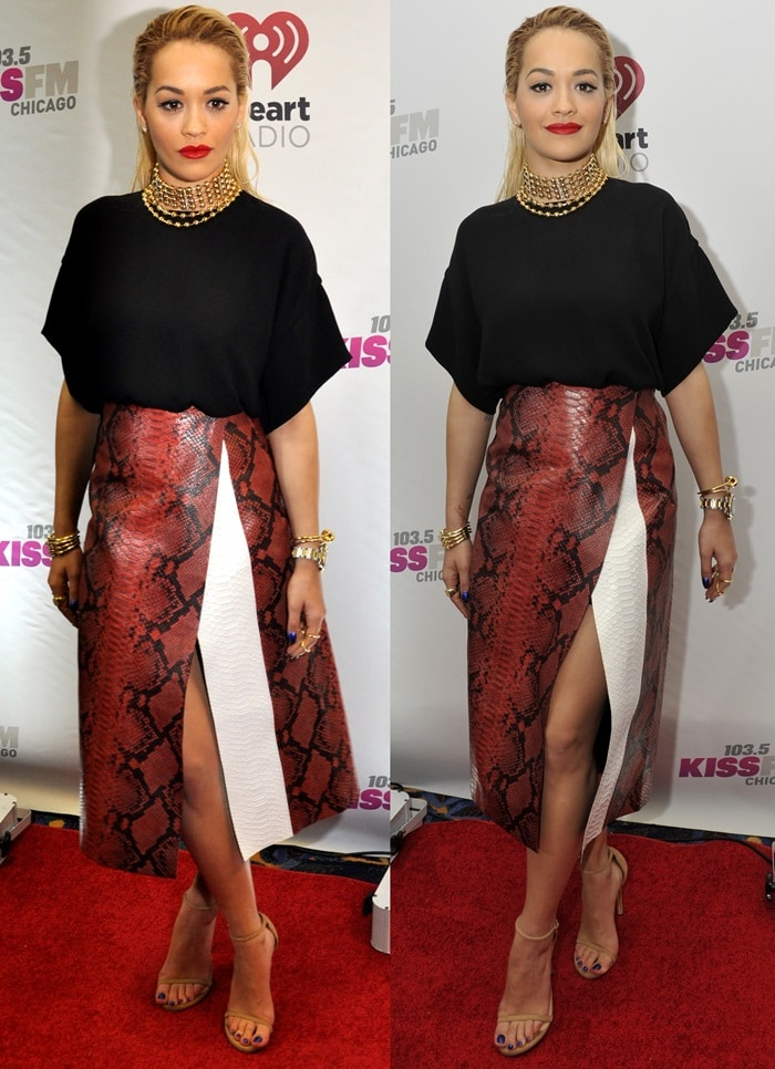 Rita Ora flaunts her legsin a black draped top and a red python skirt with a thigh-high slit