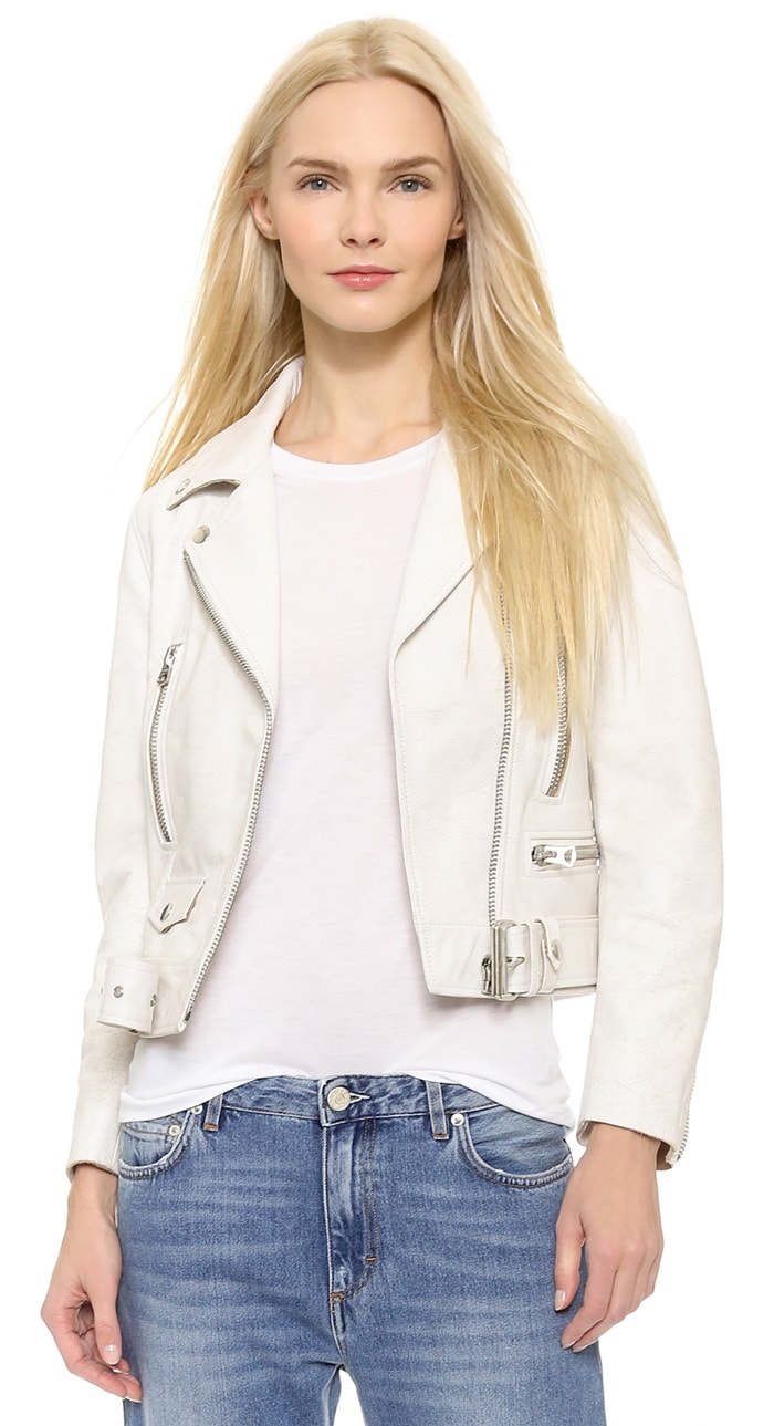 Studded, notched lapels and an off-center zip placket lend classic appeal, and the belted hem offers a casual edge. 3 zip pockets and a tiny snap-flap pocket detail the front