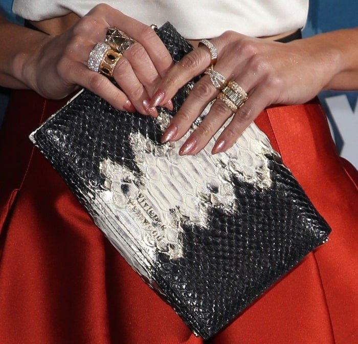Jennifer Lopez shows off a slew of rings as she holds a clutch