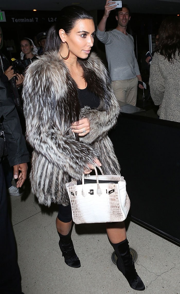 Kim Kardashian in knee-length leggings, a sheer long-sleeved top, and a luxurious designer fur coat