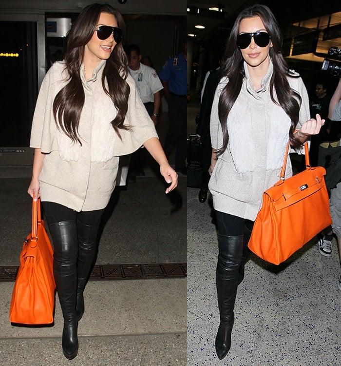 Kim Kardashian totes an orange Hermes handbag