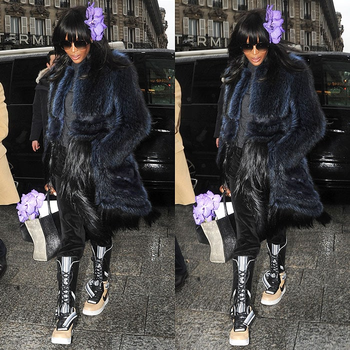 Naomi Campbell wearing a black-and-blue fur coat, black velvet sweatpants, and Nike x Riccardo Tisci Air Force 1 sneaker boots