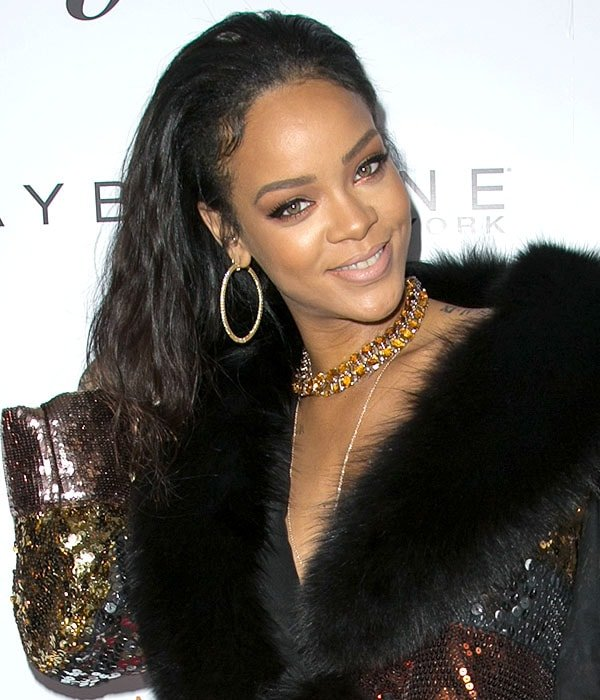Rihanna fixing her hair while posing for the cameras at The Daily Front Row Fashion Los Angeles Awards Show