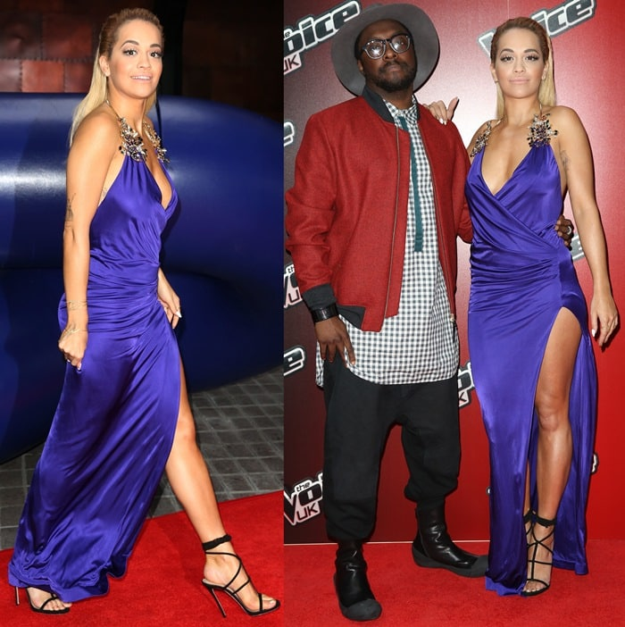 Rita Ora, posing with will.i.am, flaunts her legs in a navy silk jersey gown