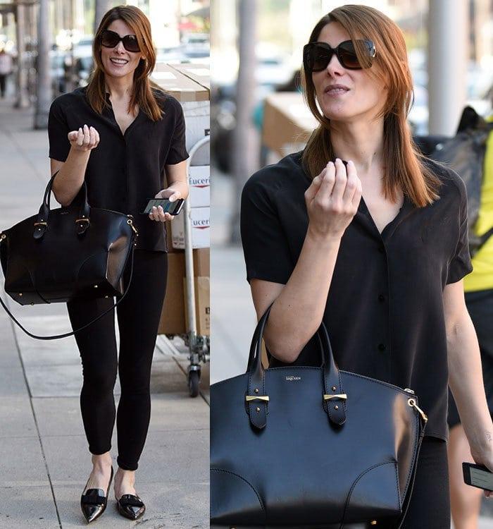 Ashley Greene wears a black blouse, leggings, and flats