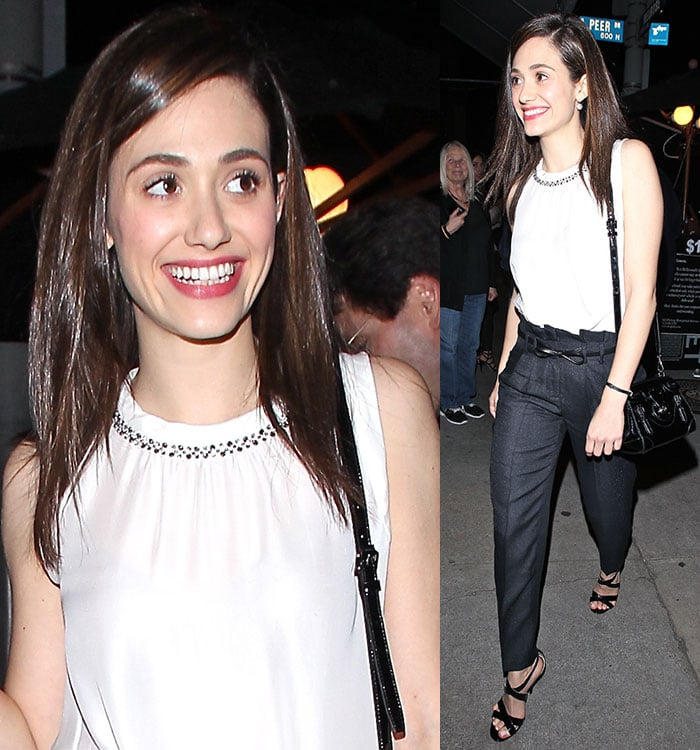 Emmy Rossum in a white sleeveless blouse tucked into high-waist black pants