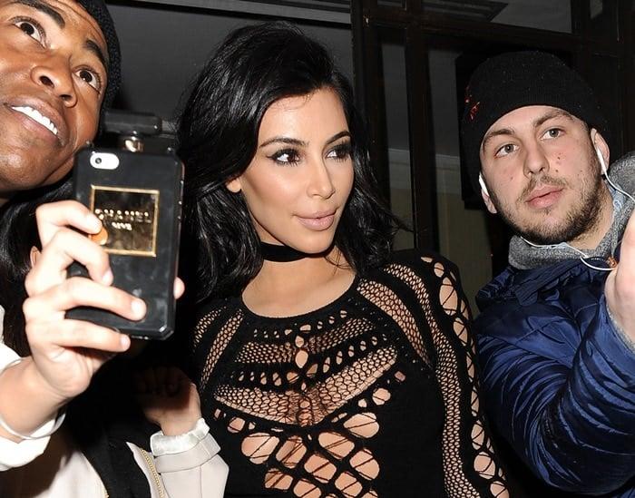Braless Kim Kardashian ina one-piece cut out jumpsuit