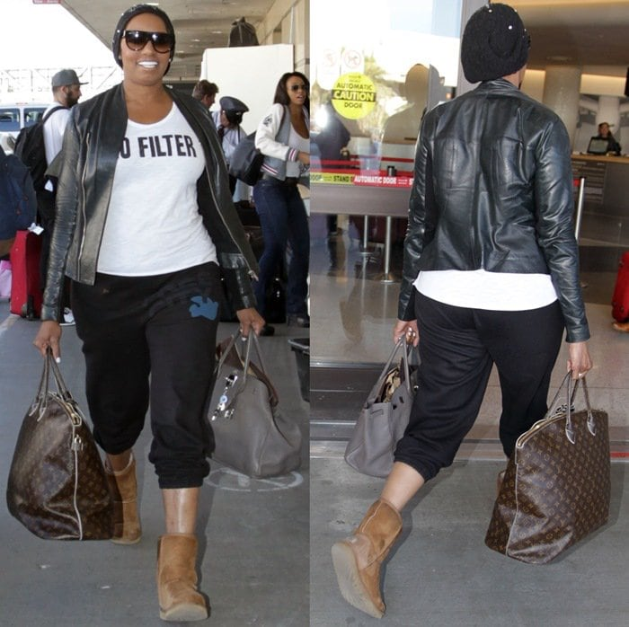 NeNe Leakes in black tracksuit pants toting a Louis Vuitton carryall