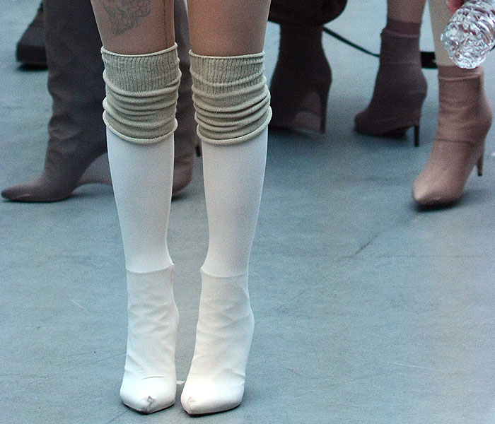 Models wearing ankle boots and tall boots covered in socks and pantyhose at the Yeezy fashion show