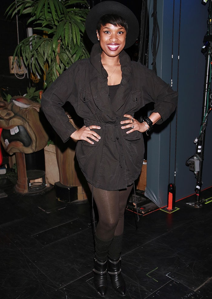 Jennifer Hudson in an oversized coat, a low-cut top, and stockings