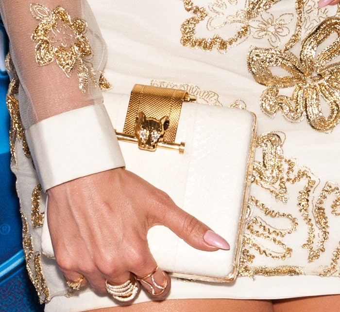 Jennifer Lopez carries a gold-embellished clutch as she shows off her pink manicure and gold rings
