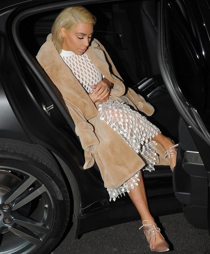 Kim Kardashian showed off her breasts in a white mesh fishnet dress