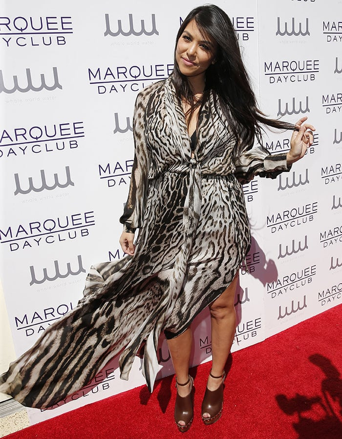 Proving that she's the best-dressed Kardashian, Kourtney arrived at the luxury resort casino and hotel in a floor-length Roberto Cavalli leopard-print chiffon wrap dress, which gave us a peek at her black halter bikini underneath