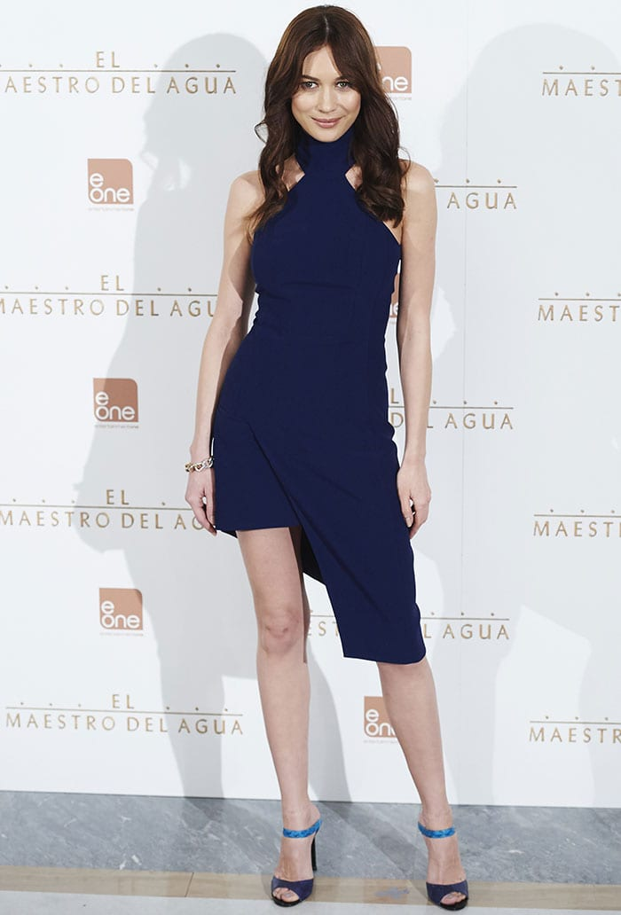 Olga Kurylenko's dress features an edgy asymmetrical hemline that put her long, slender legs on display
