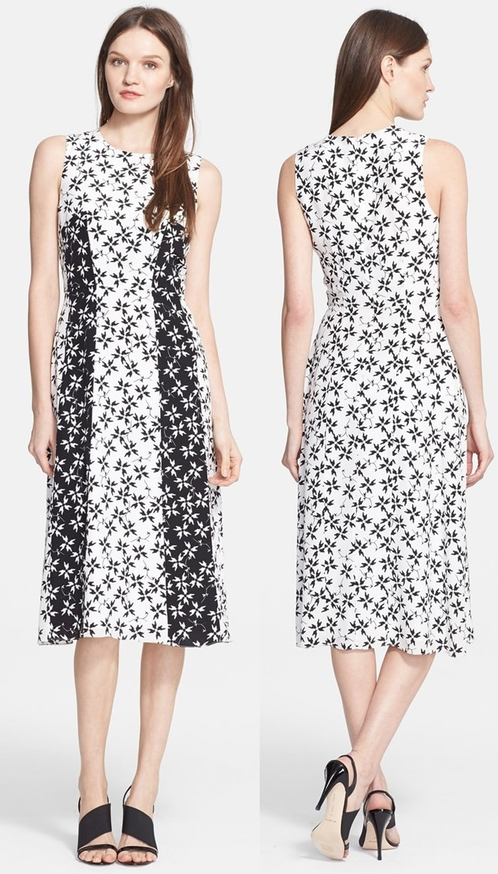 Black panels streamline the silhouette and further the graphic styling of a knee-length silk dress patterned in energetic pinwheels.