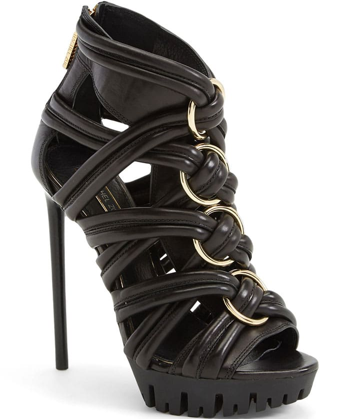 Twisted straps of soft leather further the rocker edge of a sky-high stiletto sandal grounded by a lugged sole