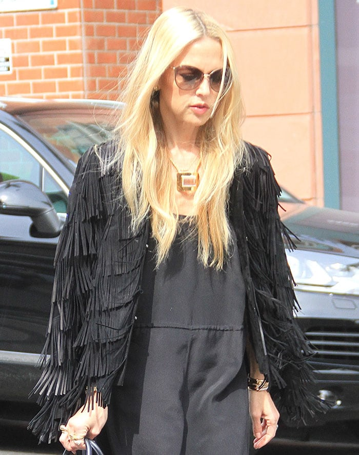 Rachel Zoe draping a black fringed jacket over her shoulders