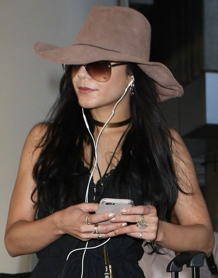 Actress Vanessa Hudgens tries to go incognito as she wears a wide-brimmed hat and aviator sunglasses at Los Angeles International Airport (LAX) while listening with her earphones on February 25, 2015