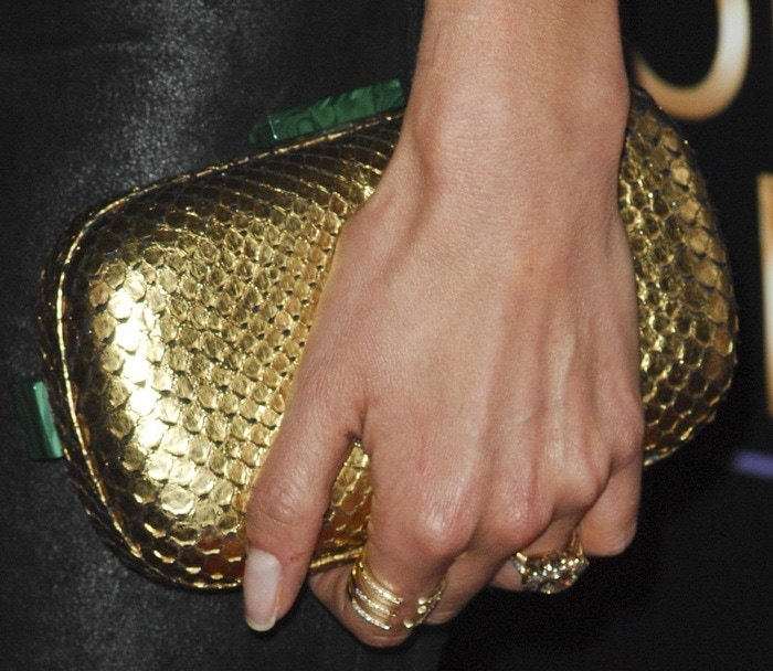 Nikki Reed complements her gold Corto Moltedo clutch with a selection of gold rings