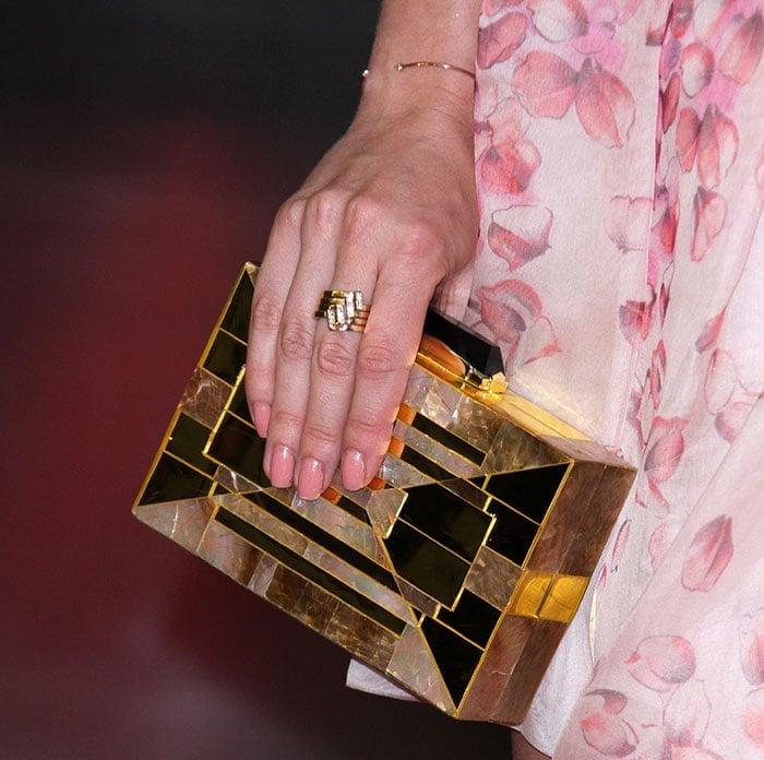 Anna Camp toted a gold Kotur clutch