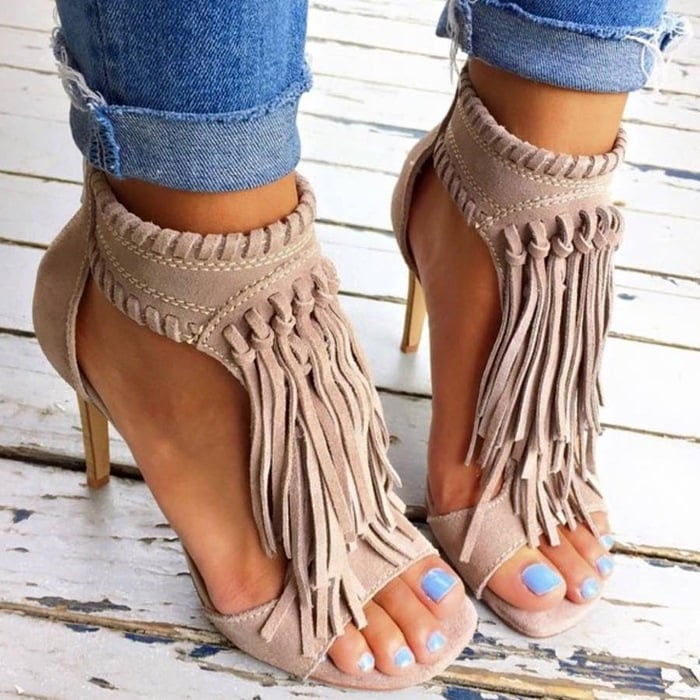 Dramatic fringe adds movement and vintage attitude to a sleek suede T-strap sandal accented with whipstitched trim