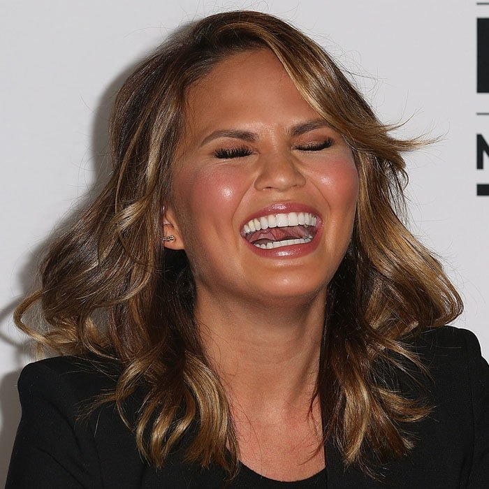 Chrissy Teigen laughing heartily at a joke during the Twitter press conference