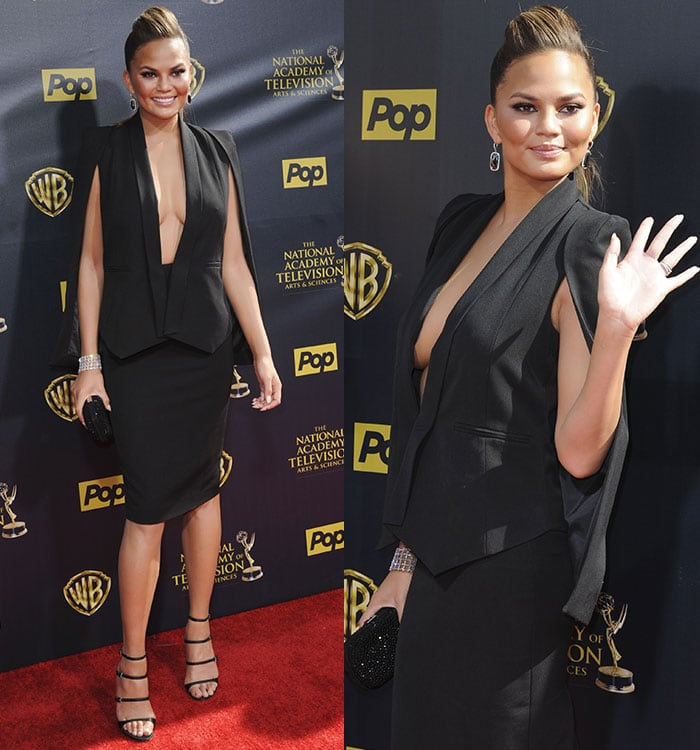 Chrissy Teigen flashed cleavage in a plunging cape blazer with a pencil skirt
