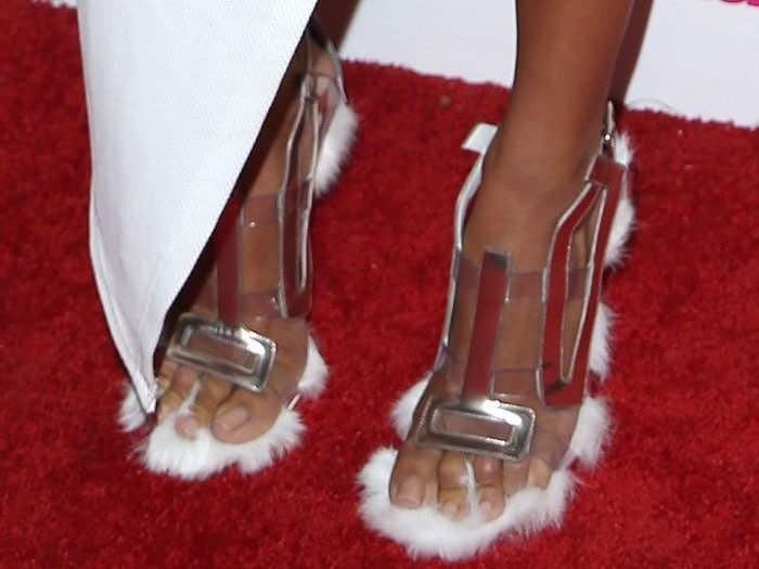 Draya Michele's feet in Gianmarco Lorenzi clear-and-metallic-strap sandals with side fur trim