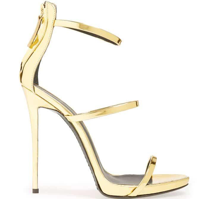 Slender goldtone straps highlight a sophisticated pointy-toe sandal set on a slim stiletto heel