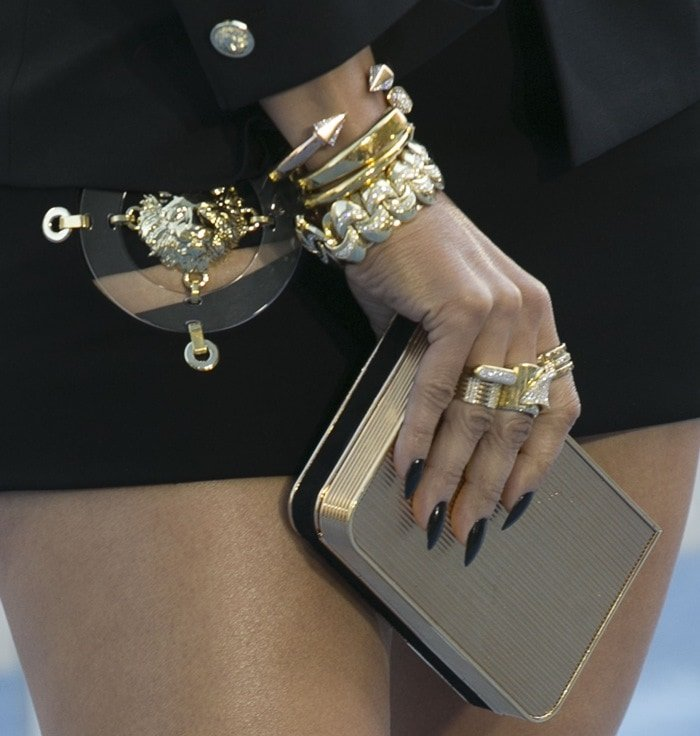 Jennifer Lopez toted a Salvatore Ferragamo clutch and accessorized with numerous bangles and rings