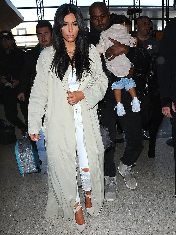 The Wests making their way through a throng of paparazzi inside LAX