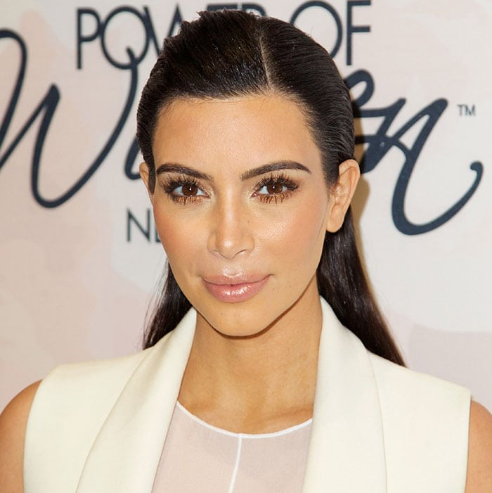 Kim Kardashian wore her hair slicked back with a side part