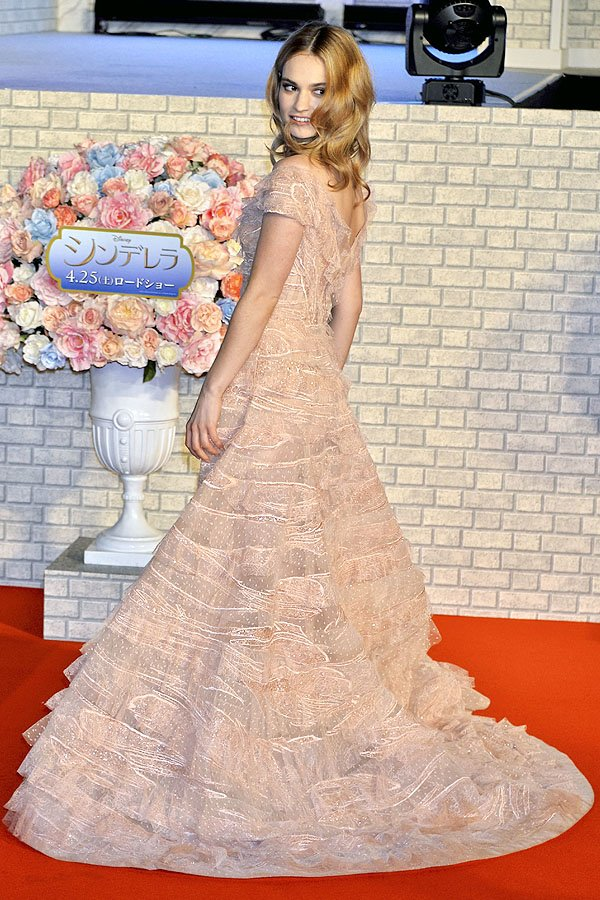 Lily James showing the back of her peach-colored Elie Saab Spring 2015 couture tiered ruffle gown