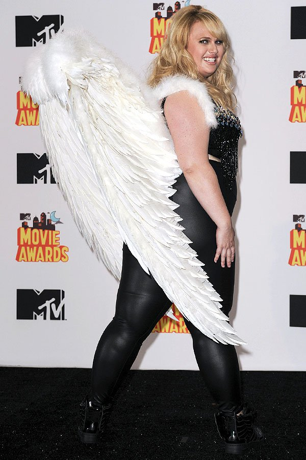 Rebel Wilson modeling white wings, a bedazzled black bra, black liquid leather leggings, and black winged sneakers