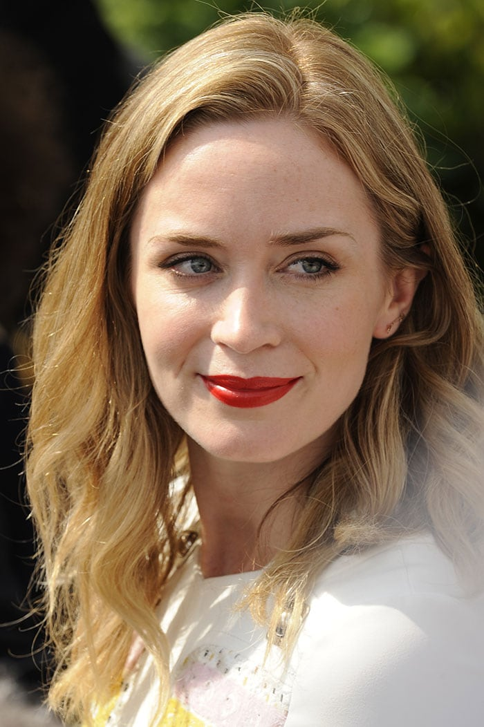 Emily Blunt wore her short blonde hair down in loose waves and opted for a bright red lip shade