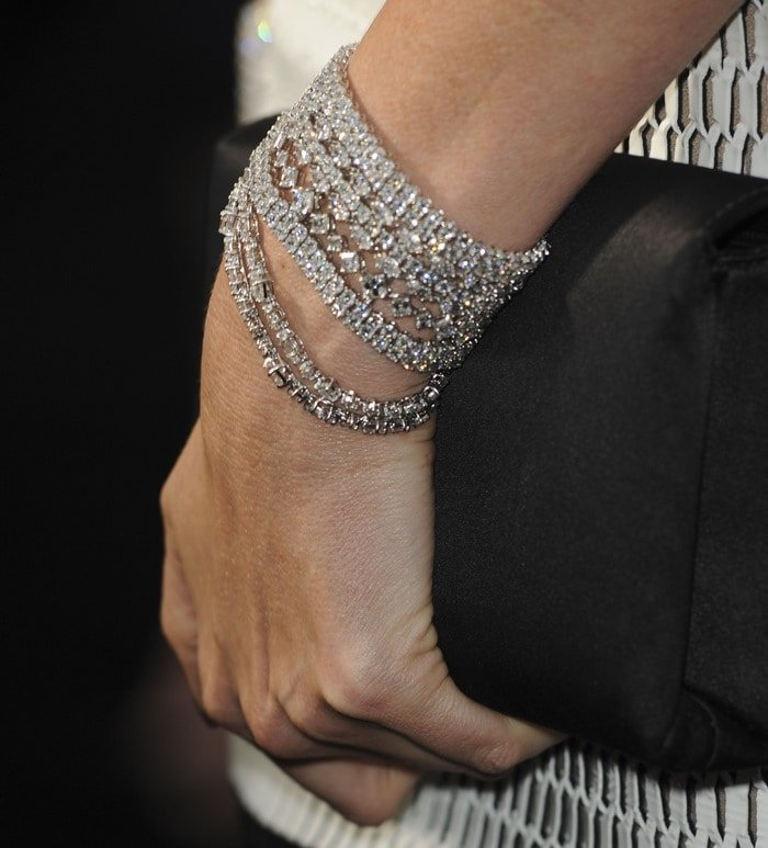 Charlize Theron showing off a black clutch and glittering Harry Winston bracelets