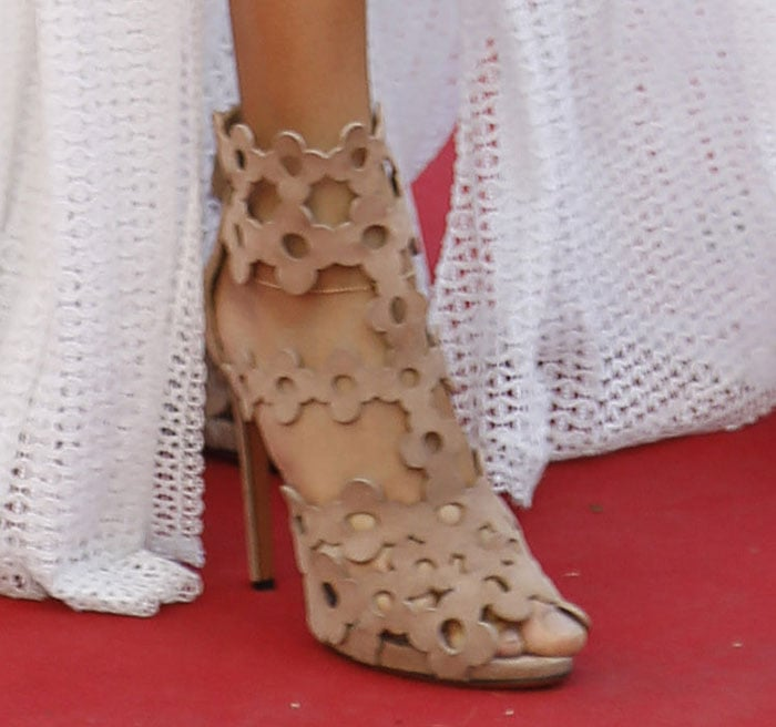 Joan Smalls's nude chamois leather sandals feature floral cutout details