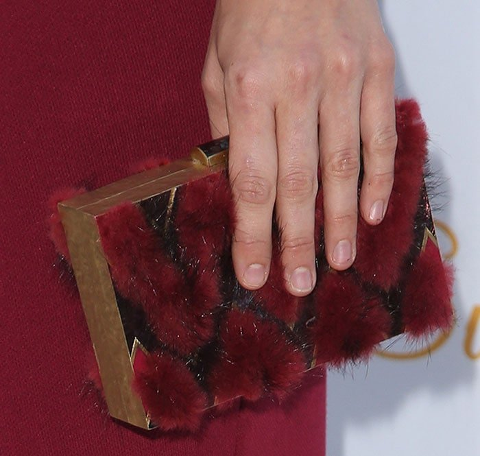 Katharine McPhee toting a box clutch featuring furry red details