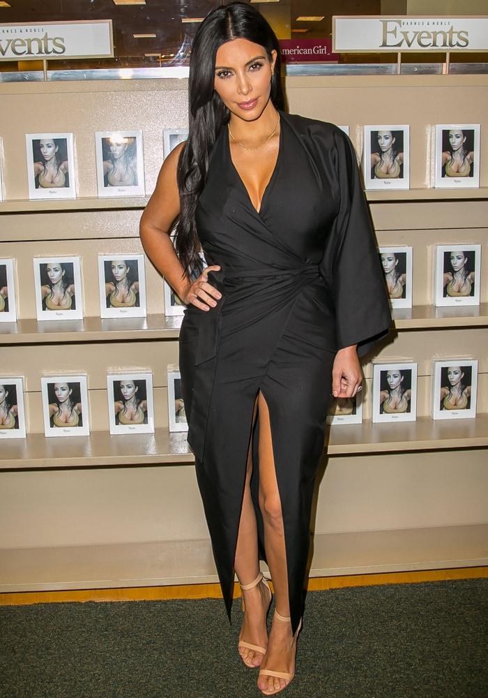 Kim Kardashian was wearing a gorgeous asymmetrical black wraparound dress with a center slit