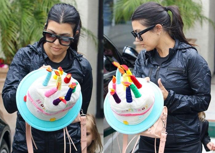 Kourtney Kardashian carrying a Happy Birthday cake decoration