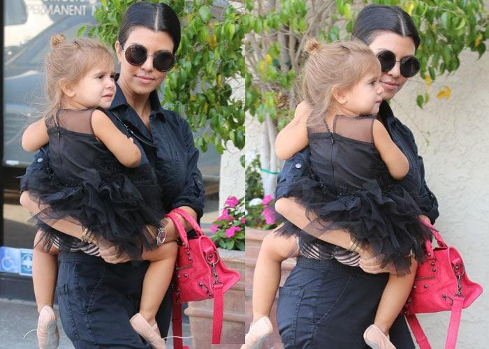 Kourtney Kardashian carrying the adorable Penelope Scotland Disick into the dance studio