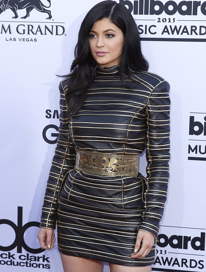 Kylie Jennerin a structured black leather mini dress from the Balmain Pre-Fall 2013 collection