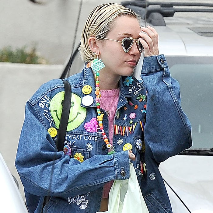Miley Cyrus rocking heart-shaped sunglasses, a long dangling earring, and an embellished denim jacket