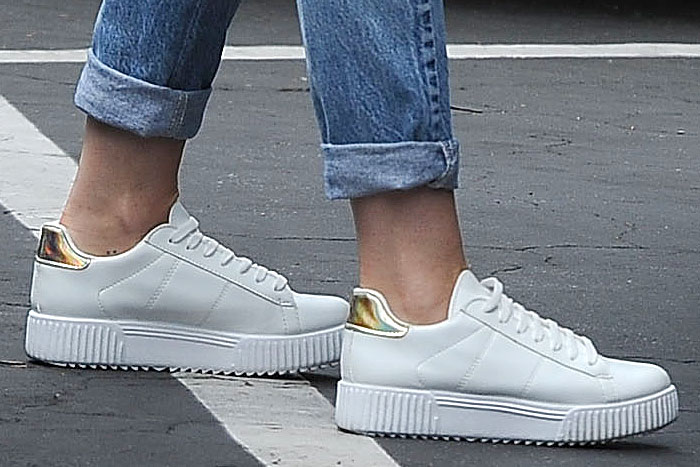 Miley Cyrus' white River Island platform sneakers with holographic gold trims on the padded heels
