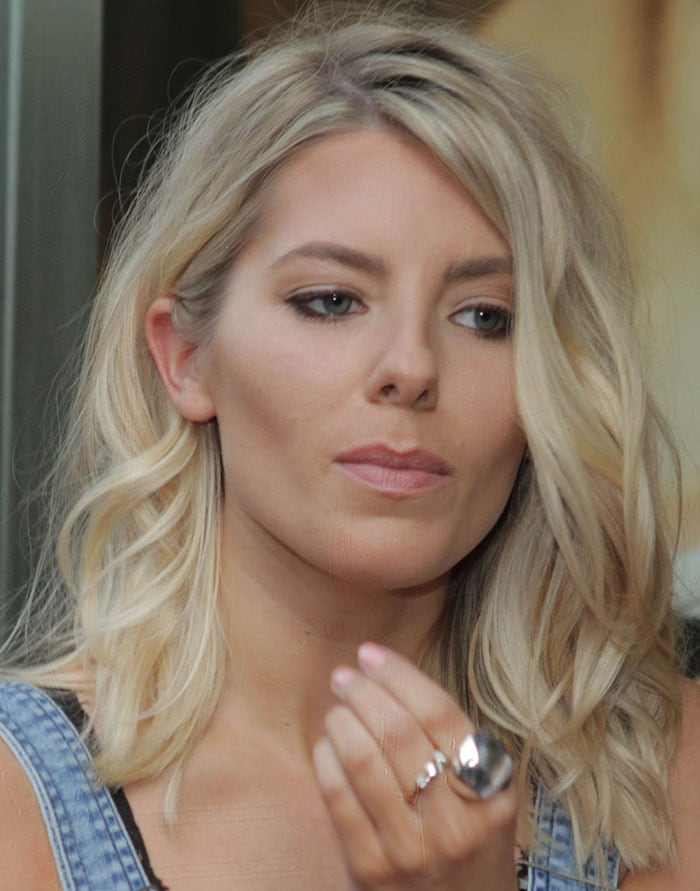 Mollie King styled her hair in tousled waves with side parting