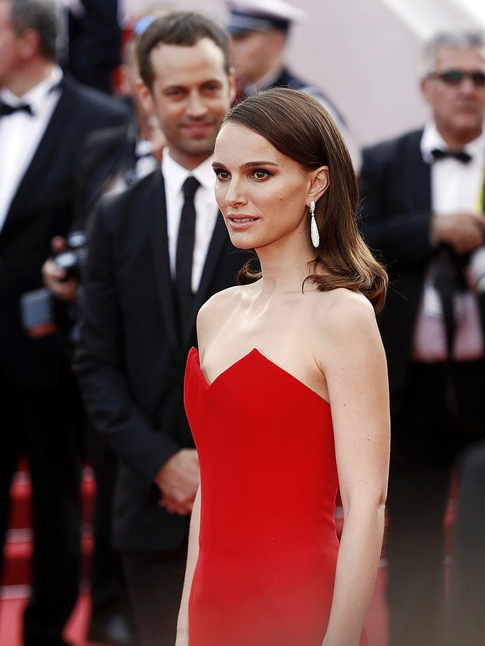 Natalie Portman posing on the red carpet as husband Benjamin Millepied looks on