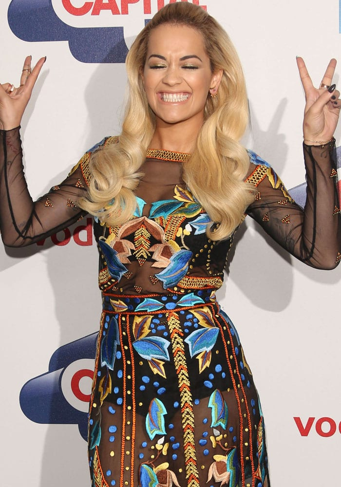 Rita Ora's index and middle fingers are raised and parted to make a V shape