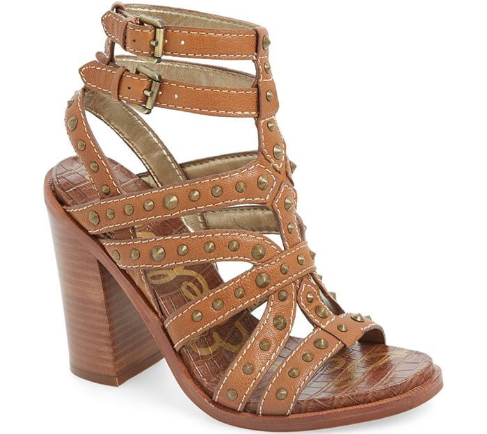 Polished cone studs play up the edgy attitude of a dramatic stacked-heel sandal topped with twin ankle straps